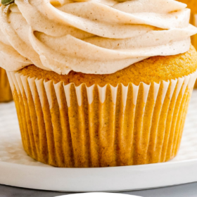 Up close image of pumpkin cupcakes on a white plate with wording on top for Pinterest.