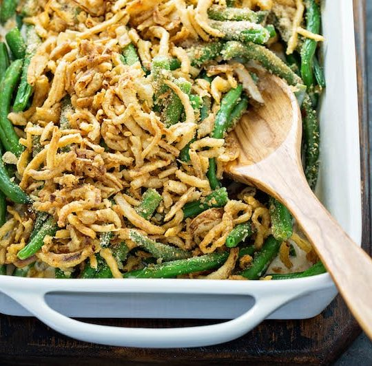Green Bean Casserole in a white casserole dish with a wooden spoon in it.
