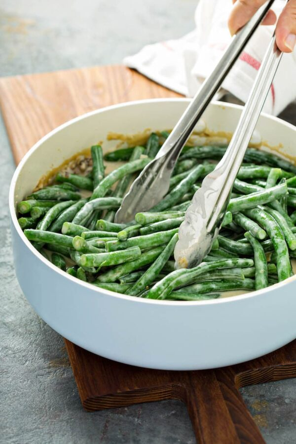 Green beans tossed in homemade cream of mushroom soup in a skillet with tongs for green bean casserole recipe.