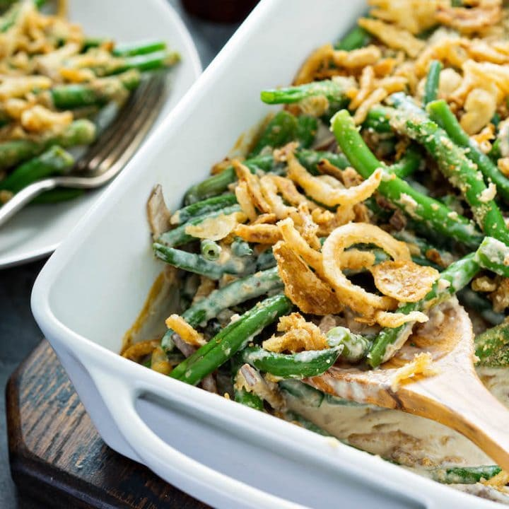 Green Bean Casserole topped with french fried onions in a white baking pan with a wooden spoon removing a serving