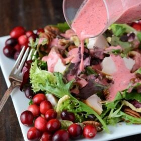 Turkey Salad with Cranberry Vinaigrette on a white plate with a fork - dressing being pour over salad