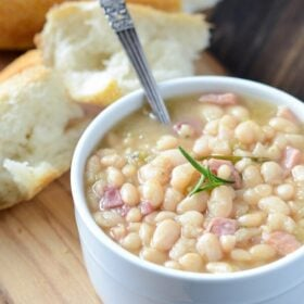 Rosemary Ham Bean Soup in a white bowl with a spoon and bread