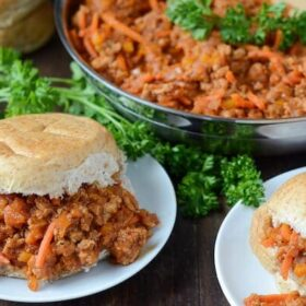 Lightened Up Turkey Sloppy Joes on white plates. Sloppy Joe mix in a skillet.