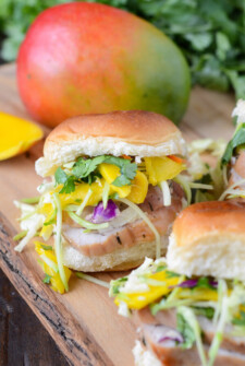 Pork Tenderloin Sliders with Spicy Mango Slaw on a wooden board.
