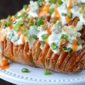 Buffalo Hasselback Potatoes topped with buffalo sauce, sour cream and chives.