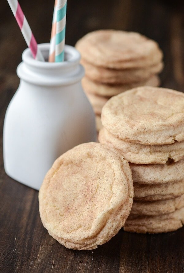 Two stacks of snickerdoodle cookies next to a white jar with straws