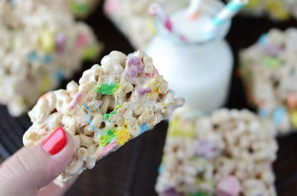 A Hand Holding a Lucky Charm Marshmallow Treat Over a Platter Displaying More Cereal Bars