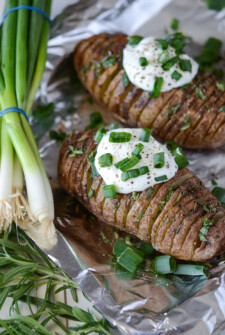 Rosemary Hasselback Potatoes topped with sour cream and scallions