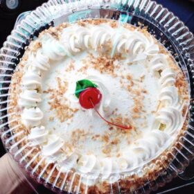 Coconut Cream Pie topped with whipped cream and a cherry