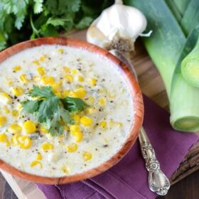 Creamy Sweet Corn and Roasted Poblano Soup in a wooden bowl with a spoon, garlic, and leeks