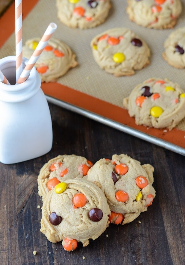 Three Reese's Pieces Peanut Butter Cookies piled in front of a baking sheet with more cookies on it