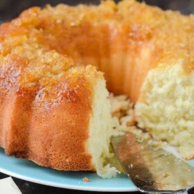 A Pineapple Coconut Bundt Cake on a blue plate with a slice missing