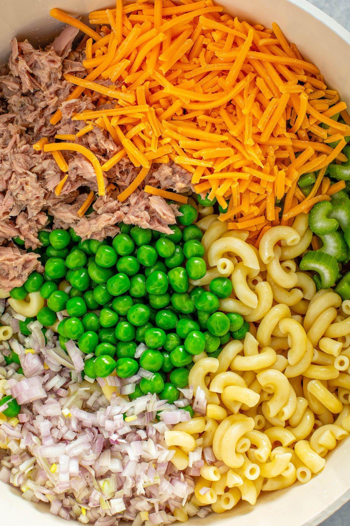 Bowl full of cheese, peas, macaroni, tuna, and more.
