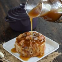 Donut Bread Pudding on a white plate with a spoon and Rum Sauce being poured over it