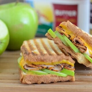 Apple, Cheddar & Turkey Panini on wooden board with apples in the background