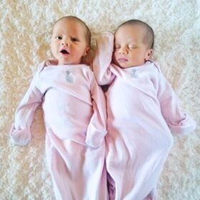 Newborn twin girls in long sleeved pink pajamas