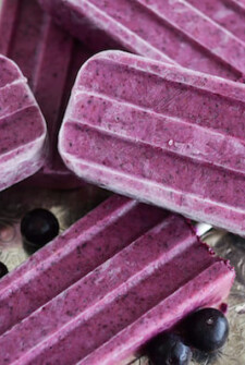 Blueberry Ginger Popsicles on a silver platter with blueberries