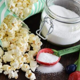 Sweet & Salty Kettle Corn in green and white bags with a jar of sugar and measuring spoons with sugar