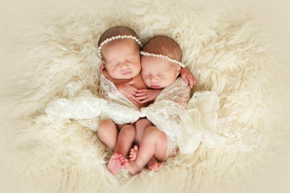 Two Newborn Baby Girls Cuddling on a Fluffy Blanket