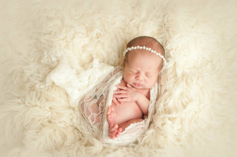 A Newborn Baby Resting on Top of a Fluffy White Surface