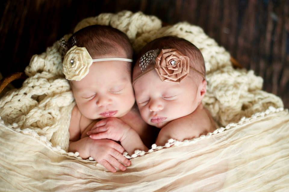 Newborn Twins with Floral Headbands in a Rocker with Comfy Off-White Blankets