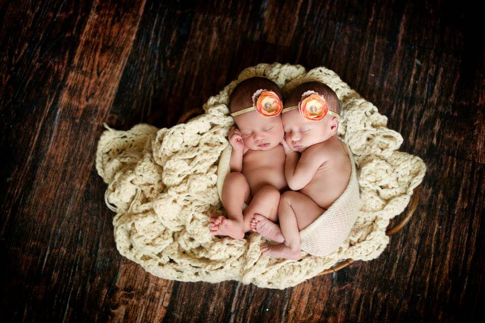 Two Baby Girls Sleeping on a White Knitted Blanket with Flower Headbands on their Heads