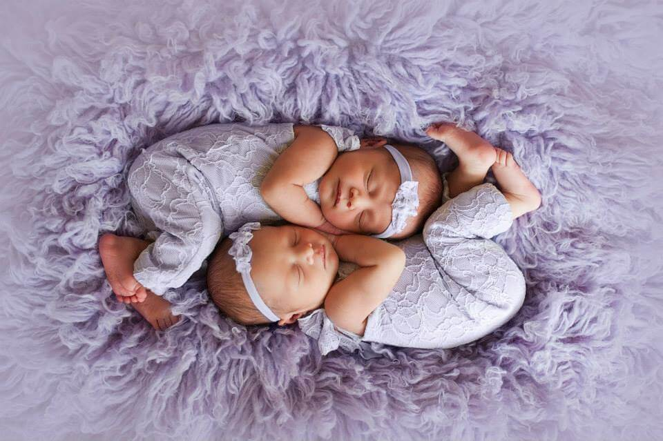 Newborn Twins Sleeping with Lilac Outfits on a Purple Blanket