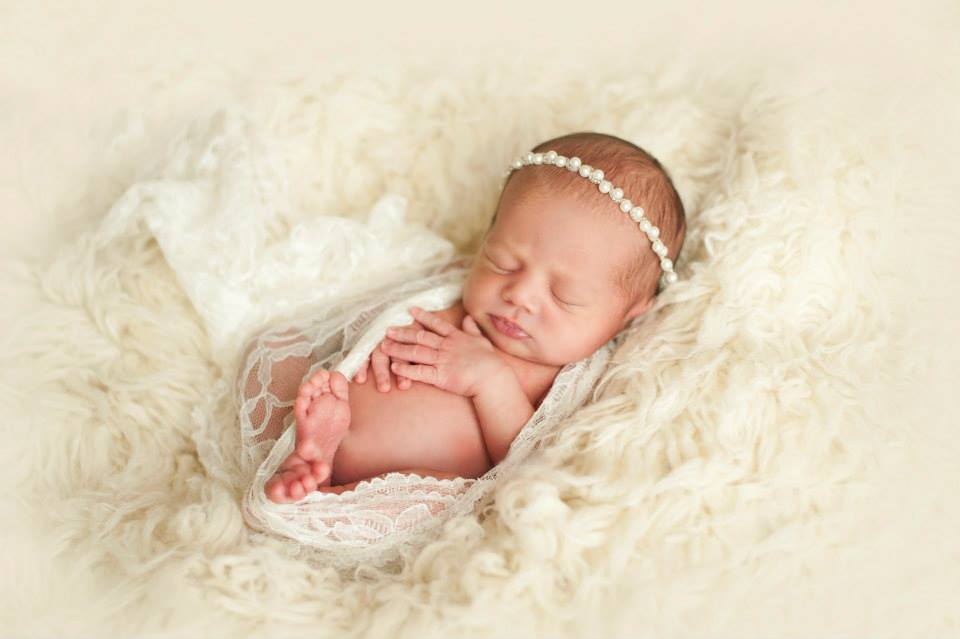 A Newborn Girl Wrapped Loosely in Lace and Sitting on a Fluffy Surface