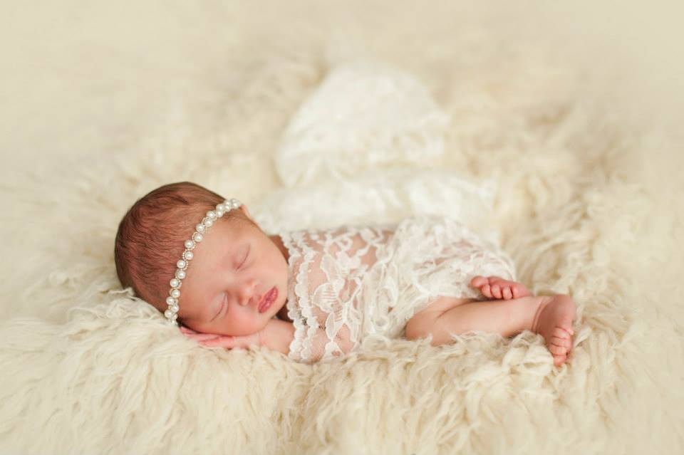 A Sleeping Baby Girl with White Lace Draped Over Her