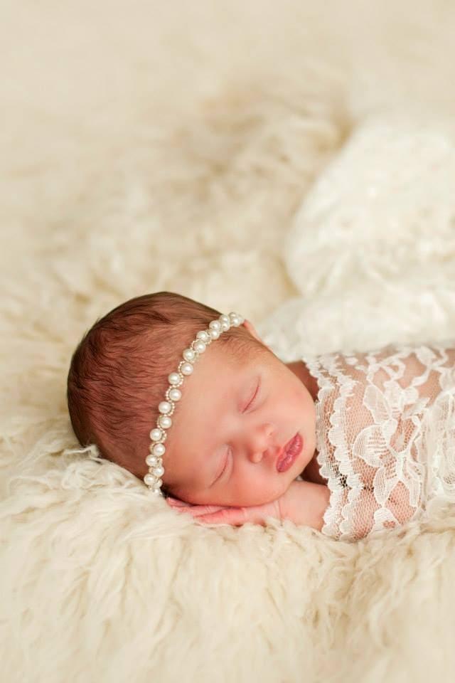 A Newborn Baby Girl Sleeping on a Fluffy Blanket with a Pearl Headband