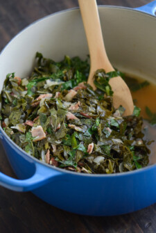 Beer Bacon Collard Greens in a blue pot with a wooden spoon