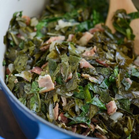 Collard Greens in a large blue pot with bacon and a wooden spoon