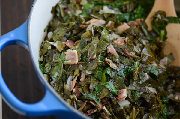 A blue pot filled with collard greens and bacon