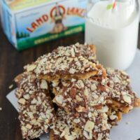 A Pile of Almond Roca Bark Pieces Next to a Glass of Milk