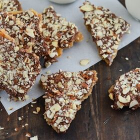 Pieces of Almond Toffee Candy Scattered on a Wooden Surface
