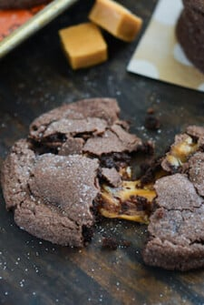 Chocolate Caramel Stuffed Cookies with caramel candies - one cookie broken in half showing caramel center