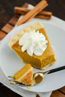 Buttermilk Pumpkin Pie topped with whipped cream on a white plate with a fork on a wooden board