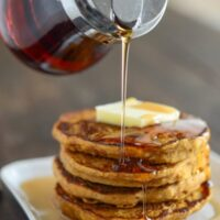 A stack of Pumpkin Pancakes on a white plate with syrup being poured over them