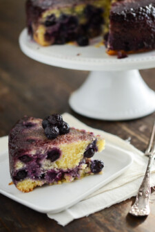 Slice of Blueberry Upside Down Cake on a white plate - remainder of cake on a white cake stand