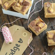"""Six Pieces of Microwave Peanut Butter Cup Fudge Set Up Beside Some Twine and Cardboard Tags Labeled """"Fudge"""""""