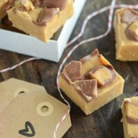 Microwave Reese's Peanut Butter Fudge on a wooden surface with homemade gift tags and string