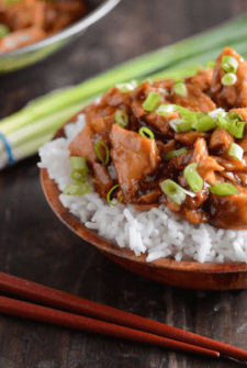 Crockpot Bourbon Chicken served over rice with chopsticks and scallions