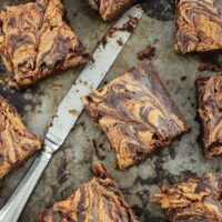 Swirled brownies cut into squares on a cookie sheet with a knife.