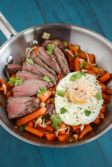 A frying pan filled with sweet potato fries, steak and a fried egg