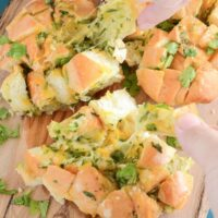 A loaf of cheesy bread with cilantro being pulled apart piece by piece