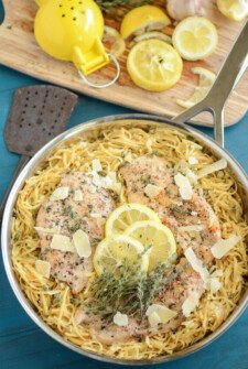 Lemon Thyme Chicken served over pasta, topped with lemon, shaved parm, and rosemary in a skillet