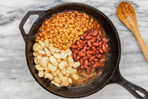 Three types of baked beans in a cast iron skillet.
