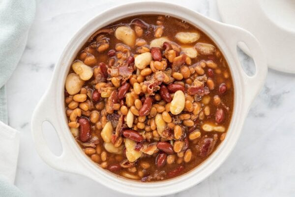Baked beans in a white casserole dish before baking.