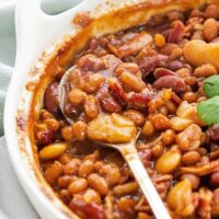 A spoonful of baked beans in a casserole dish.