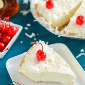 Slice of Boozy Piña Colada No Bake Pie on a white plate with a fork topped with shredded coconut and a cherry
